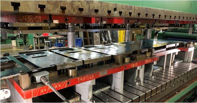 Progressive stamping die for an aluminum frame